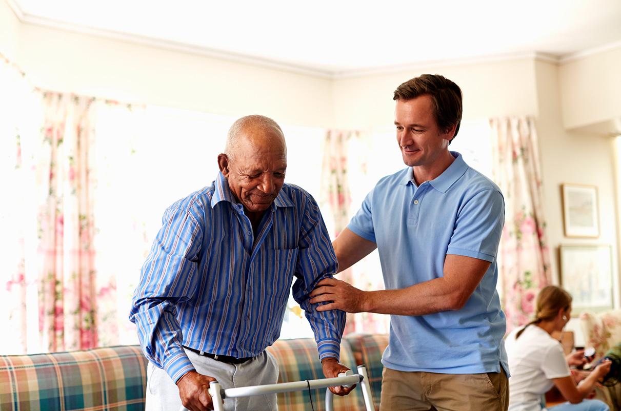 A photo of a volunteer helping an elderly man.